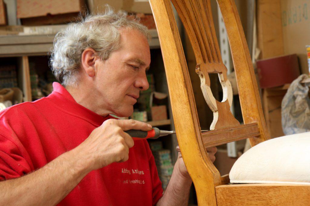 Man repairing a wooden chair wearing Abbey Group sweatshirt 3