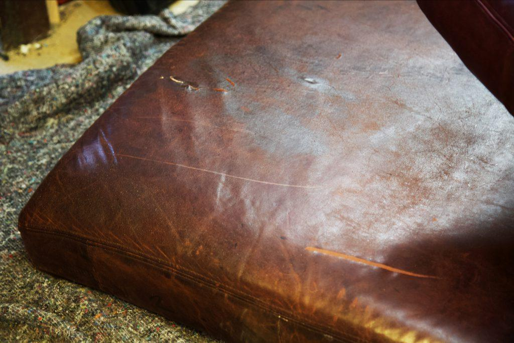 Close up of tears and scratches on leather cushion