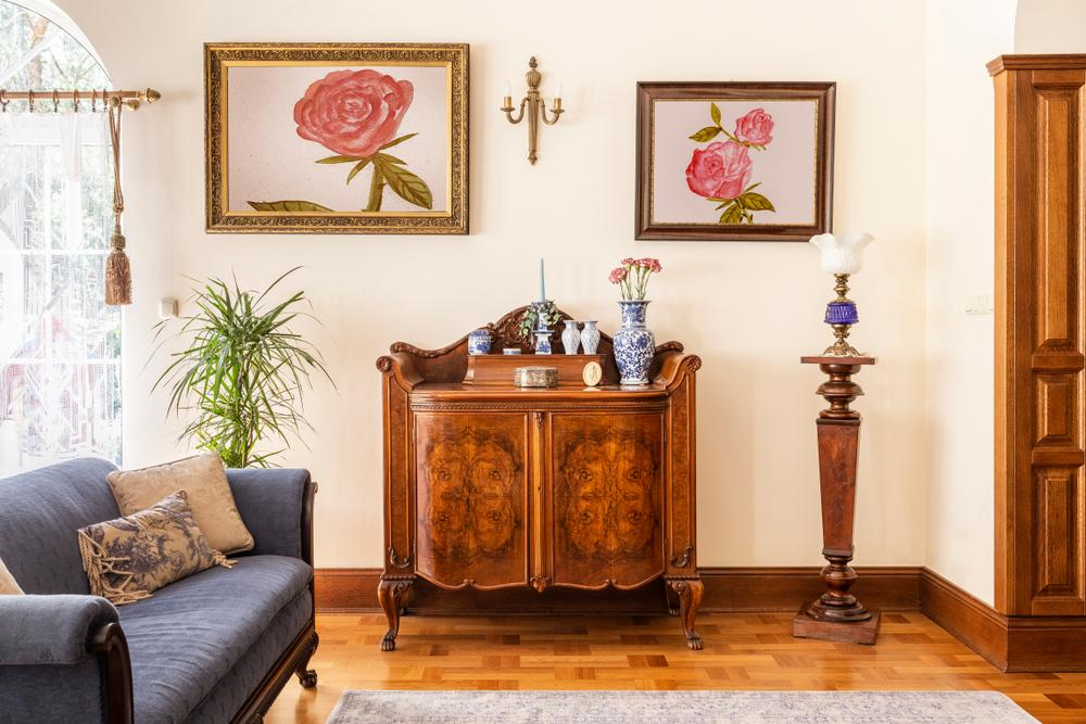 Antique sideboard in living room with pictures above