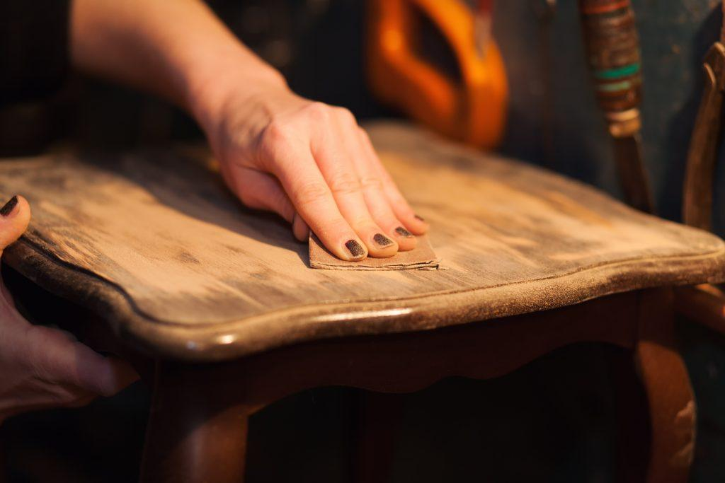 Woman sanding an antique side table