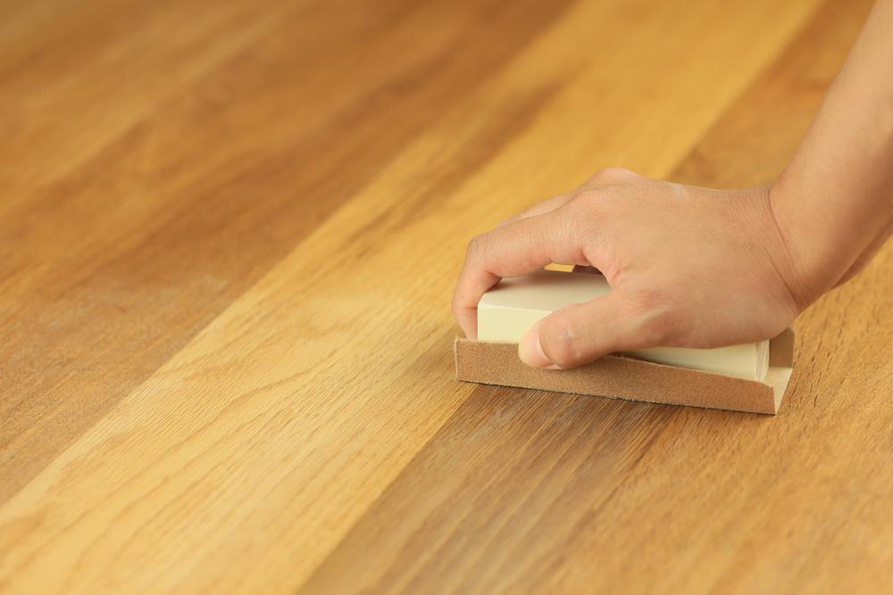 man restoring wooden floor with sandpaper
