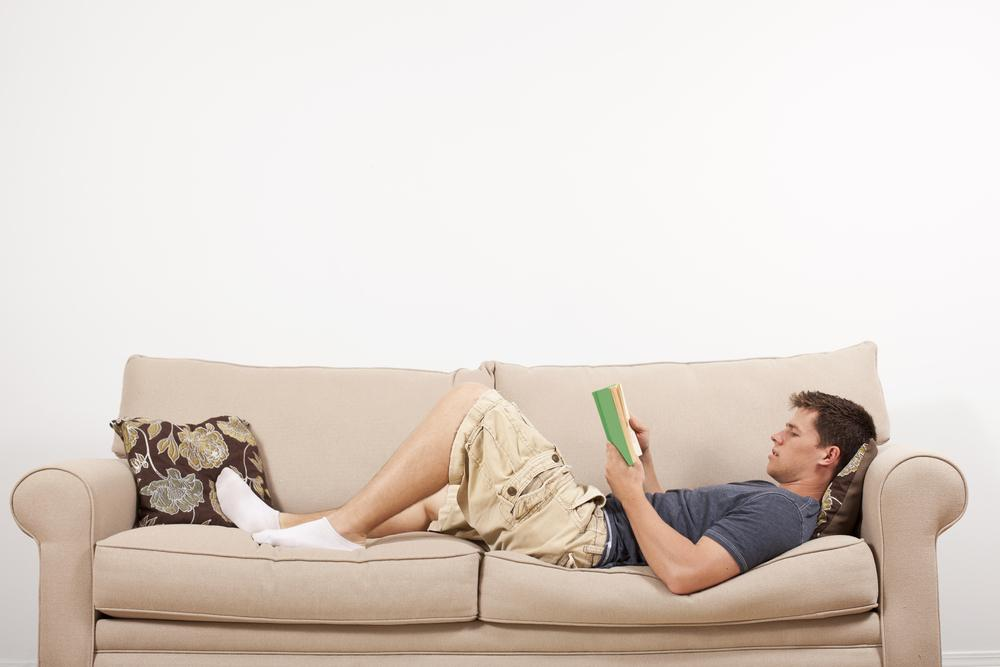 a,young,man,lays,down,and,reads,on,a,couch