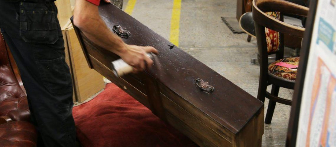 Man spraying front of drawers with two handles