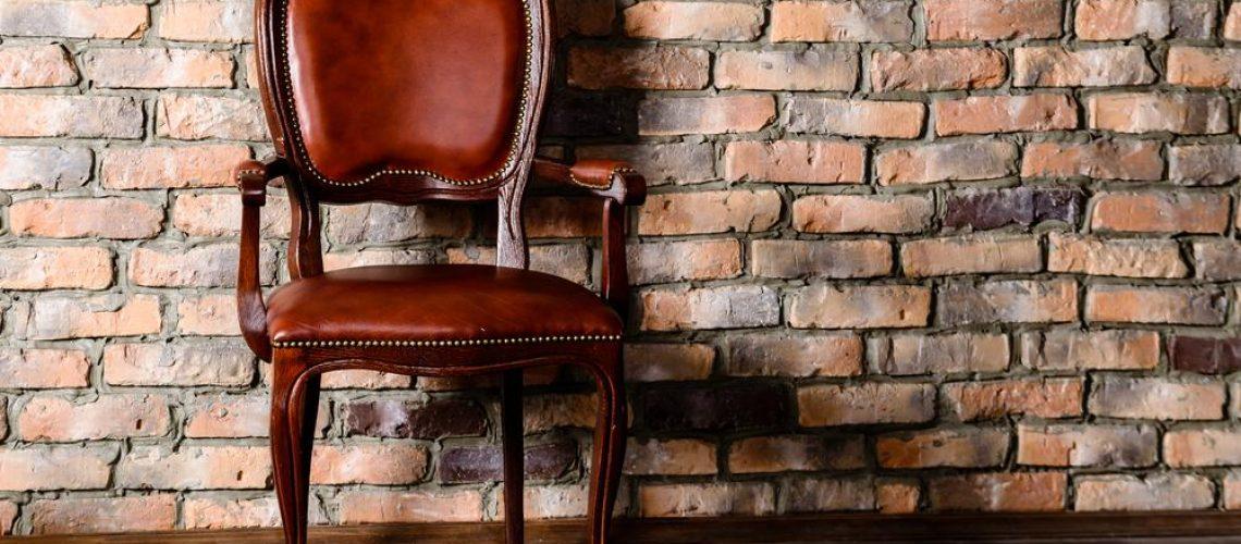 Antique chair against an interior brick wall